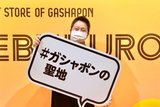 ハッシュタグボードを持ってすてきな笑顔を浮かべる飯塚さん。