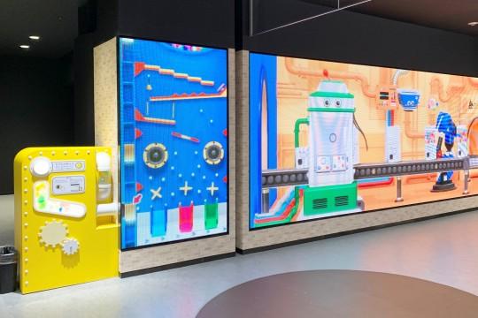 エントランスではカプセルトイの組立工場をイメージした映像が流れていますが、左の投入口から空のカプセルを入れることでモニターに変化が! 小さな子どもは特に喜びそう。