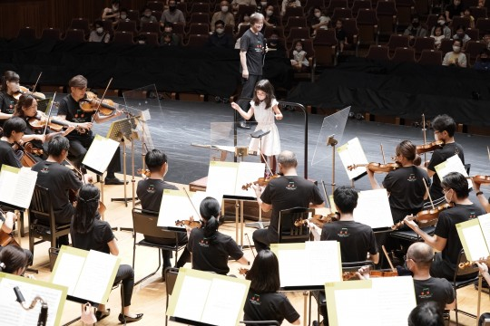In the conducting experience corner, a 6-year-old girl conducts the orchestra