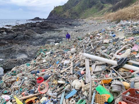 藤元氏と海岸の大量のプラスチックゴミ